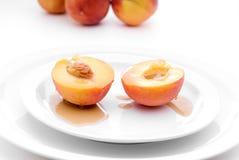 Perziken met stroop op witte plaat Stock Fotografie
