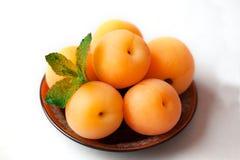 Perziken op een plaat met munt Stock Foto