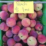 Perziken voor verkoop $1 bij landbouwersmarkt Stock Foto's