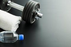 Pesa de gimnasia, botella de agua y toalla blanca imagenes de archivo