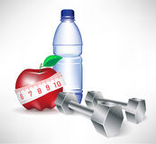 Pesa de gimnasia con la botella de agua y la manzana con medida Foto de archivo libre de regalías