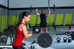 Pesa de gimnasia de la muchacha y entrenamiento de la barra del levantamiento de pesas del hombre Fotografía de archivo