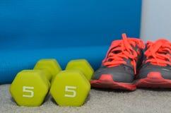 pesa de gimnasia 5lb con los zapatos del deporte y la estera del ejercicio Imagen de archivo libre de regalías
