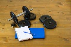 Pesa de gimnasia para el deporte con una toalla y un cuaderno para registrar los resultados, en un fondo de madera Fotografía de archivo