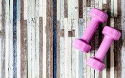 Pesa de gimnasia rosada y cinta métrica en el fondo de madera, equ del deporte Imagen de archivo