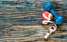 pesa de gimnasia y cinta métrica, corazón rojo en el fondo de madera, S Fotografía de archivo