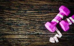 pesa de gimnasia y cinta métrica en el fondo de madera, equipmen del deporte Imágenes de archivo libres de regalías