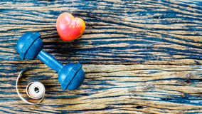 pesa de gimnasia y corazón de la cinta métrica y del rojo en el fondo de madera, S Imagenes de archivo