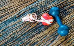 pesa de gimnasia y corazón de la cinta métrica y del rojo en el fondo de madera, S Fotos de archivo libres de regalías