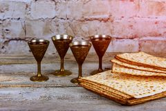Pesach Passover symbols of great Jewish holiday. Traditional matzoh, matzah or matzo and wine in vintage silver plate and glass. Retro style Stock Photo