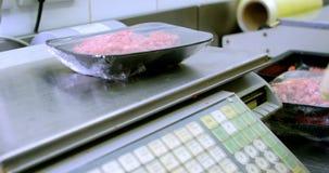 Pesaje del carnicero picadito en la balanza en la carnicería 4k almacen de video