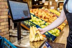Pesando bananas no supermercado imagens de stock royalty free