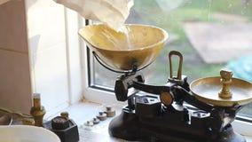 Pesando o açúcar em escalas para fazer bolos vídeos de arquivo