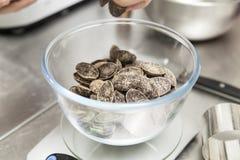 Pesando pedaços de chocolate em uma bacia fotografia de stock royalty free