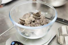Pesando pedaços de chocolate em uma bacia fotografia de stock