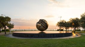 Pesaro, Italy, Square with Fountain in front of the beach. Italy, Pesaro - sculpture by Arnaldo Pomodoro at sunrise called `Tomato`s ball`. It is one of the royalty free stock photos