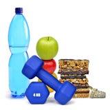 Pesas de gimnasia, botella del ANIMAL DOMÉSTICO con agua, manzanas y barras del muesli Imagenes de archivo
