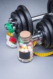 Pesas de gimnasia clásicas pesadas con la cinta métrica y las píldoras en gris Foto de archivo