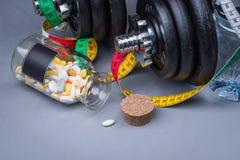 Pesas de gimnasia clásicas pesadas con la cinta métrica y las píldoras en gris Imagen de archivo