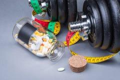 Pesas de gimnasia clásicas pesadas con la cinta métrica y las píldoras en gris Imagen de archivo libre de regalías