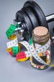 Pesas de gimnasia clásicas pesadas con la cinta métrica y las píldoras en gris Imágenes de archivo libres de regalías