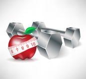 Pesas de gimnasia con la manzana y la cinta de la medida Imagen de archivo libre de regalías
