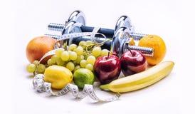 Pesas de gimnasia de Chrome rodeadas con la cinta métrica sana de las frutas en un fondo blanco con las sombras Foto de archivo libre de regalías