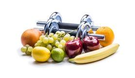 Pesas de gimnasia de Chrome rodeadas con la cinta métrica sana de las frutas en un fondo blanco con las sombras Imagen de archivo libre de regalías
