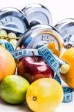 Pesas de gimnasia de Chrome rodeadas con la cinta métrica sana de las frutas en un fondo blanco con las sombras Fotos de archivo libres de regalías