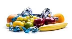 Pesas de gimnasia de Chrome rodeadas con la cinta métrica sana de las frutas en un fondo blanco con las sombras Foto de archivo