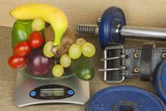 Pesas de gimnasia de Chrome rodeadas con las frutas y verduras sanas en una tabla Concepto de pérdida sana de la consumición y de Fotografía de archivo