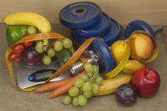 Pesas de gimnasia de Chrome rodeadas con las frutas y verduras sanas en una tabla Concepto de pérdida sana de la consumición y de Foto de archivo
