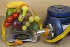 Pesas de gimnasia de Chrome rodeadas con las frutas y verduras sanas en una tabla Concepto de pérdida sana de la consumición y de Fotos de archivo libres de regalías