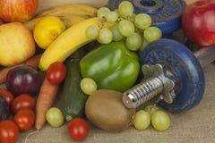 Pesas de gimnasia de Chrome rodeadas con las frutas y verduras sanas en una tabla Concepto de pérdida sana de la consumición y de Imagen de archivo