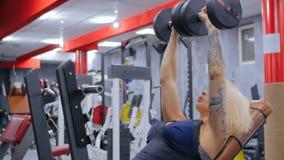 Pesas de gimnasia de elevación atléticas de la mujer joven en el gimnasio almacen de video