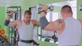 Pesas de gimnasia de elevación atléticas del hombre joven en el gimnasio almacen de metraje de vídeo