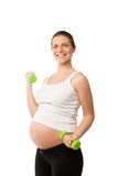 Pesas de gimnasia de elevación de la muchacha embarazada aisladas en blanco Foto de archivo