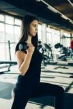 Pesas de gimnasia de elevación de la muchacha hermosa de la aptitud Muchacha deportiva de la aptitud que ejercita en gimnasio Foto de archivo