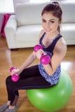 Pesas de gimnasia de elevación de la mujer apta en bola del ejercicio imagen de archivo