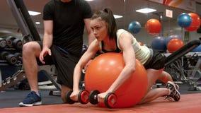 Pesas de gimnasia de elevación de la mujer con su instructor almacen de video