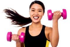 Pesas de gimnasia de elevación de la mujer feliz de la aptitud imagen de archivo