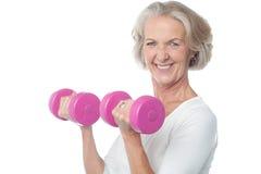 Pesas de gimnasia de elevación de la mujer feliz del ajuste imagen de archivo