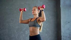 Pesas de gimnasia de elevación de la mujer joven de la aptitud en el gimnasio Mujer en ropa de deportes almacen de metraje de vídeo