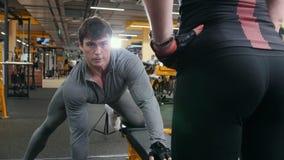 Pesas de gimnasia de elevación del hombre del atleta - el entrenamiento en el gimnasio, muchacha atractiva lo mira almacen de video