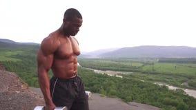 Pesas de gimnasia de elevación del hombre muscular afroamericano negro contra el fondo del cielo nublado en montañas metrajes