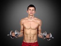 Pesas de gimnasia de elevación del hombre muscular atractivo Foto de archivo