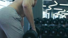 Pesas de gimnasia de elevación del hombre muy fuerte almacen de metraje de vídeo
