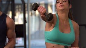 Pesas de gimnasia de elevación sonrientes de los pares musculares almacen de metraje de vídeo