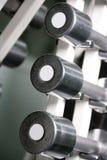 Pesas de gimnasia del cromo en una fila Foto de archivo