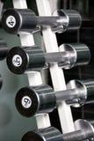 Pesas de gimnasia del cromo en una fila Imagen de archivo